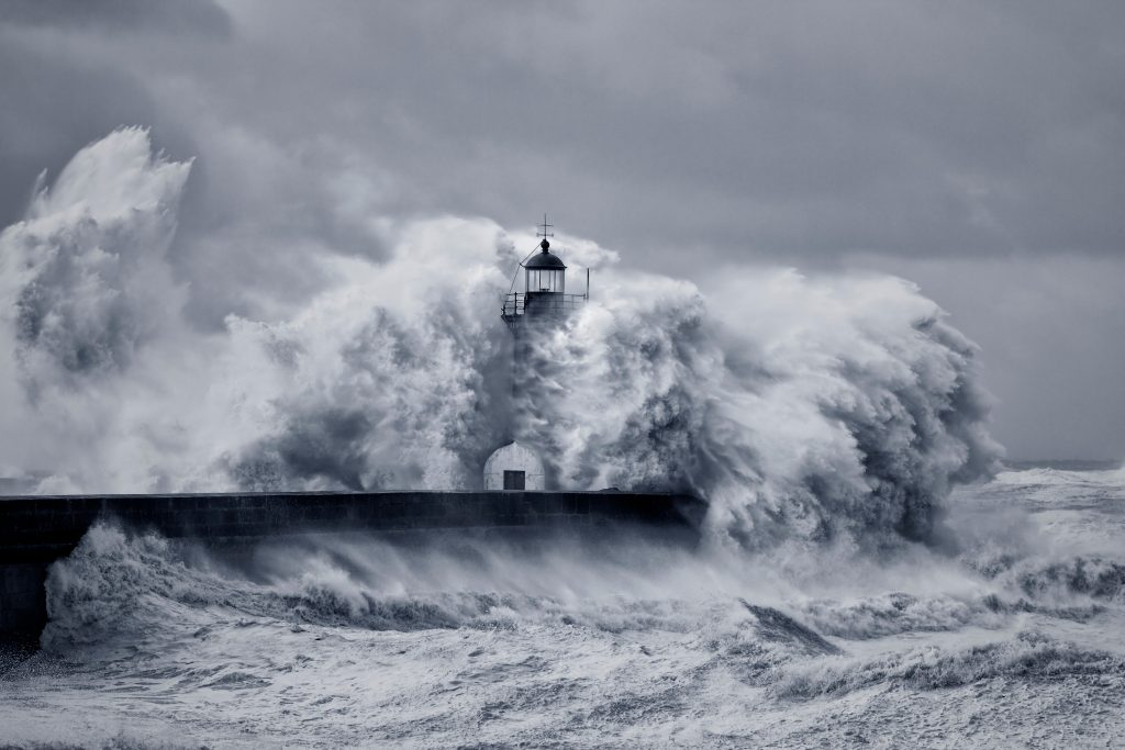 resilience: a resilient lighthouse being battered by a storm